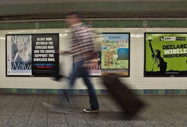 A commuter walks past an anti-Muslim poster in