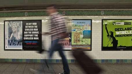 A commuter walks past an anti-Muslim poster in