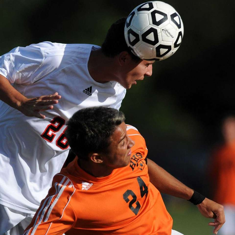 Syosset's Douglas Enga, top, heads a ball away