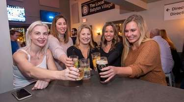 A group of friends cheers at happy hour