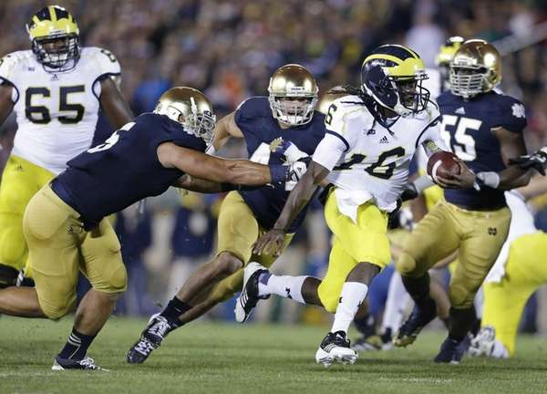 Michigan's Denard Robinson breaks the tackle of Notre