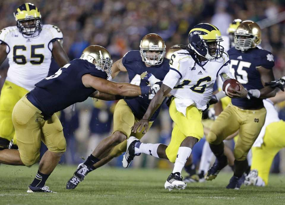 Michigan's Denard Robinson breaks the tackle of Notre