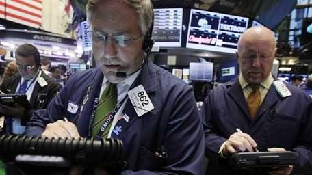 Warren Meyers, center, works with fellow traders on