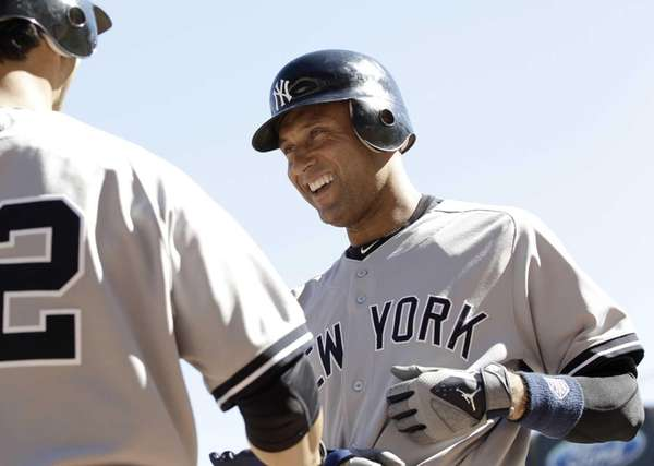 Derek Jeter, right, is congratulated by Eric Chavez