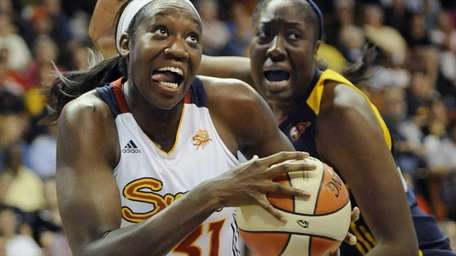 Connecticut Sun's Tina Charles, left, drives to the