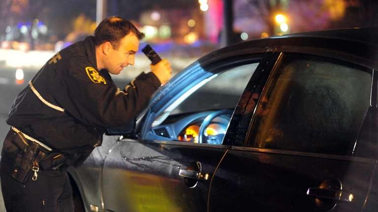 A Suffolk County deputy sheriff checks cars for