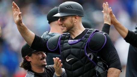 Rockies catcher Chris Iannetta is congratulated by teammates