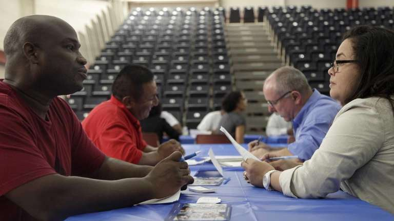 Job seekers fill out applications at a New