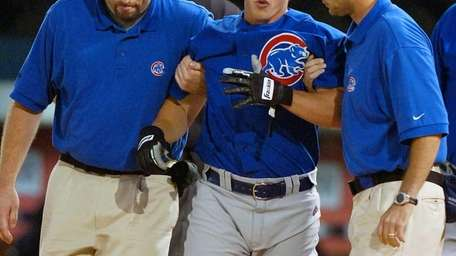 Chicago Cubs rookie Adam Greenberg, center, is helped