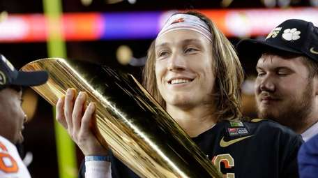 Clemson's Trevor Lawrence holds the trophy after the