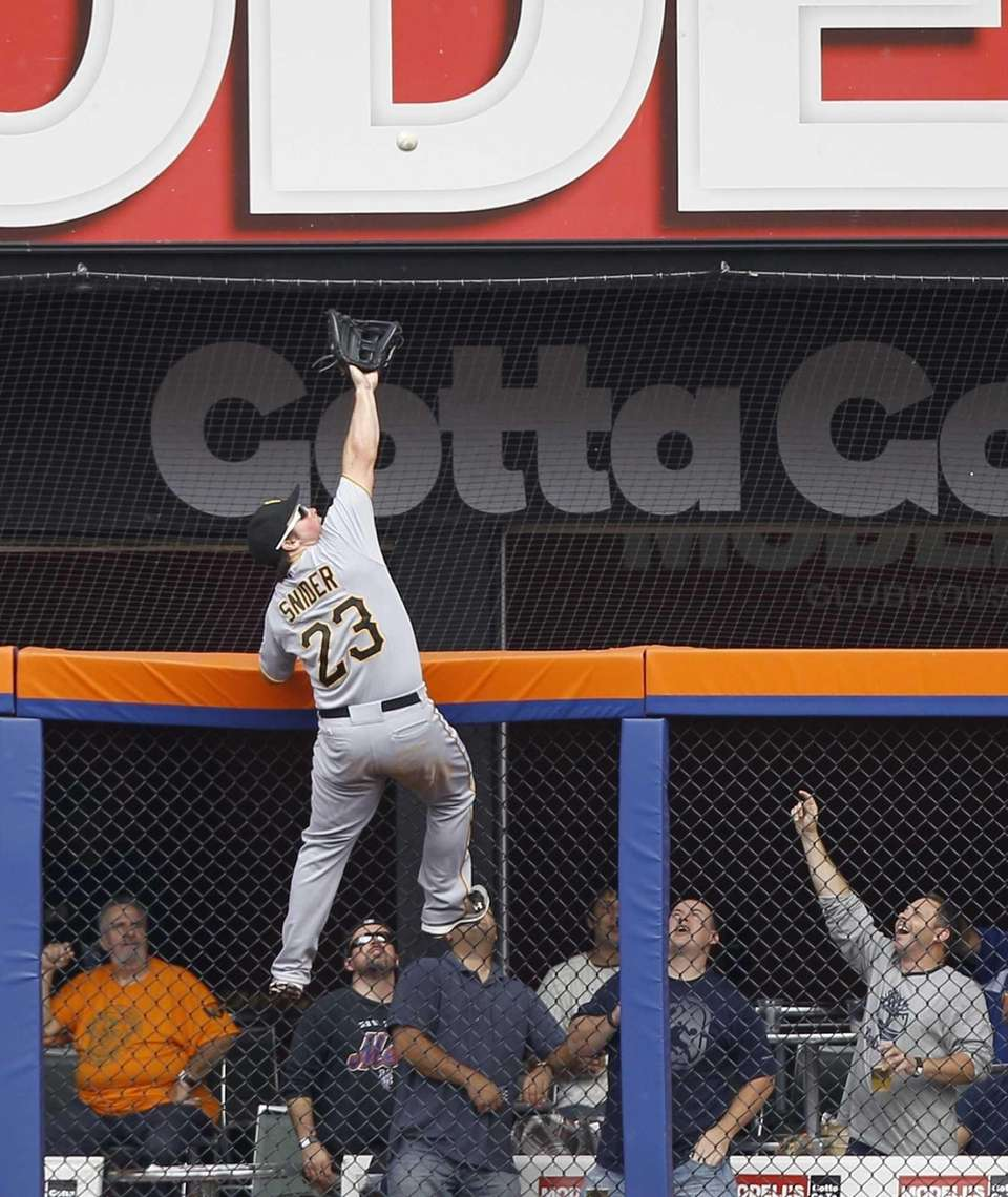 Pittsburgh Pirates right fielder Travis Snider climbs the