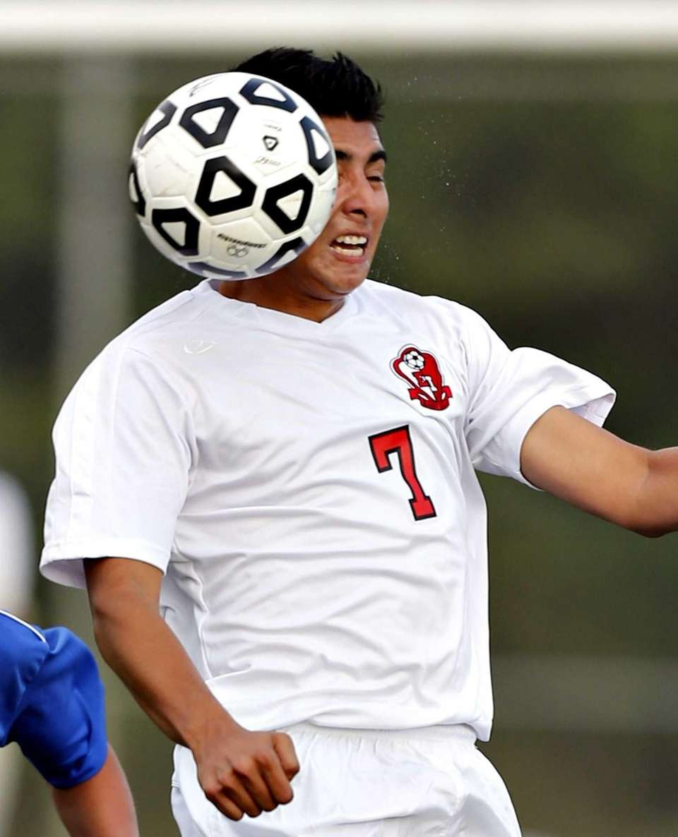 East Islip's Ulices Canessa heads the ball upfield