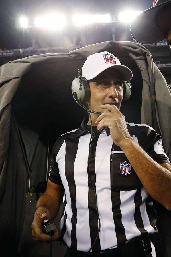 Referee Gene Steratore talks to booth officials before