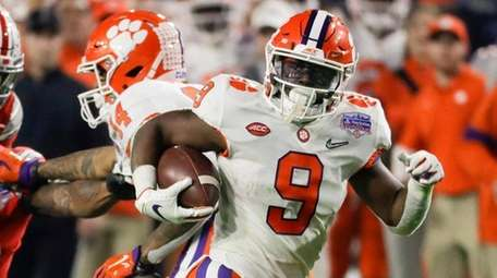 Clemson running back Travis Etienne runs for a