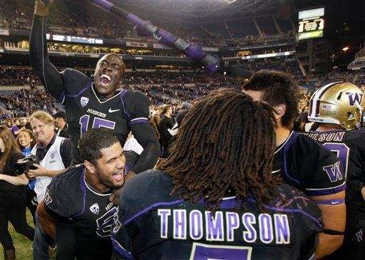 Washington's Antavius Sims, upper left, jumps on the