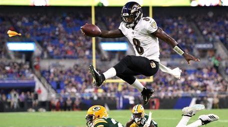Ravens quarterback Lamar Jackson leaps over Packers cornerback