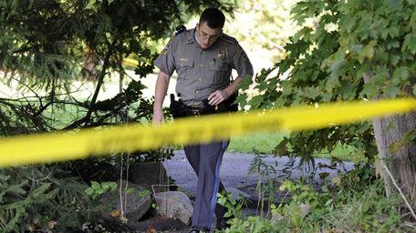 State Trooper Matt Losh emerges from the backyard