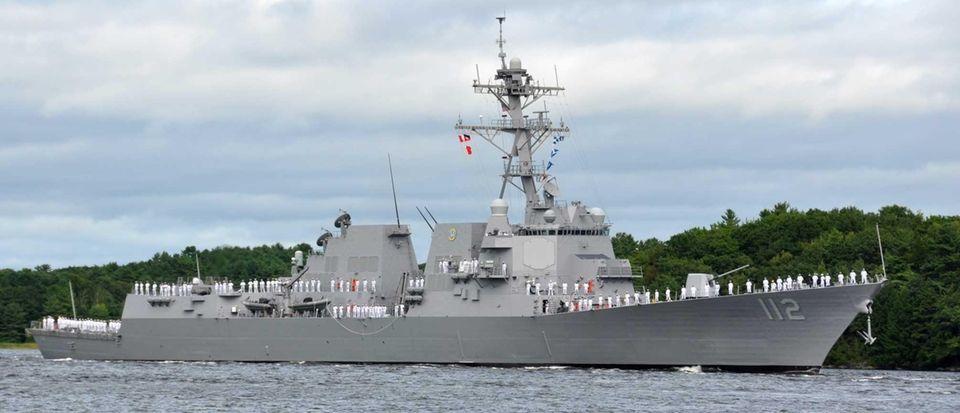 U.S. Navy sailors man the rails of the