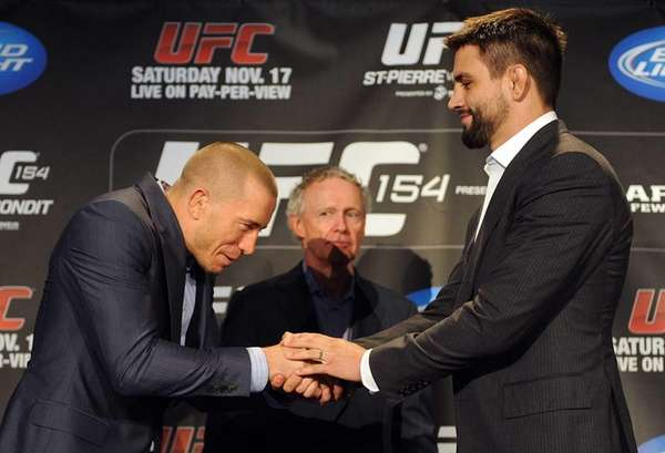Defending UFC welterweight champion Georges St-Pierre, left, shakes