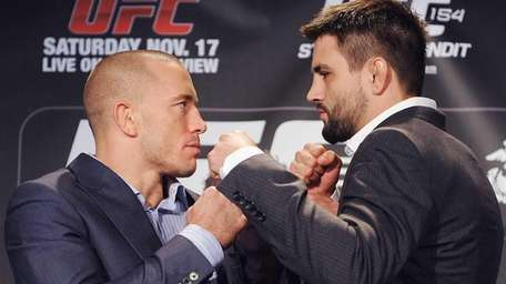Georges St-Pierre, left, squares off with Carlos Condit