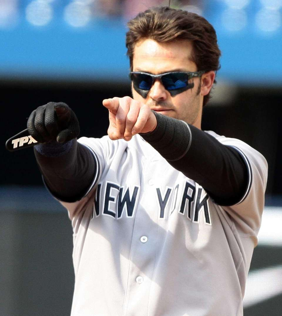 Nick Swisher points to the dugout during a
