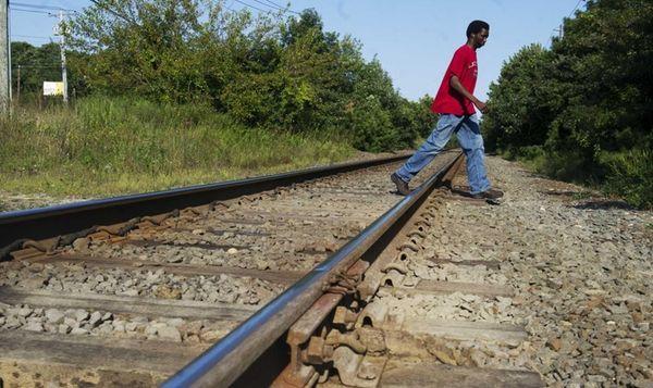 A pedestrian walks across train tracks at a