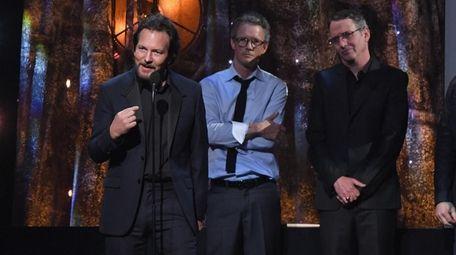 Inductee Eddie Vedder of Pearl Jam, left, speaks