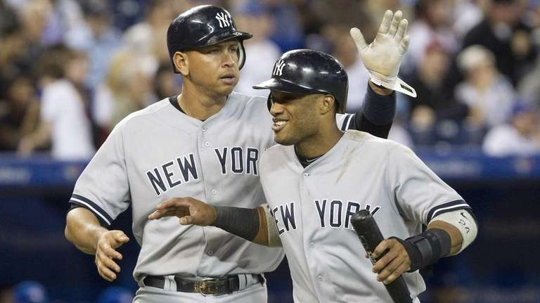 Alex Rodriguez, left, pats Robinson Cano on the