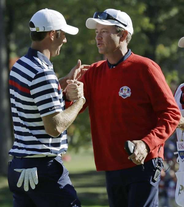 USA's captain Davis Love III congratulates Dustin Johnson