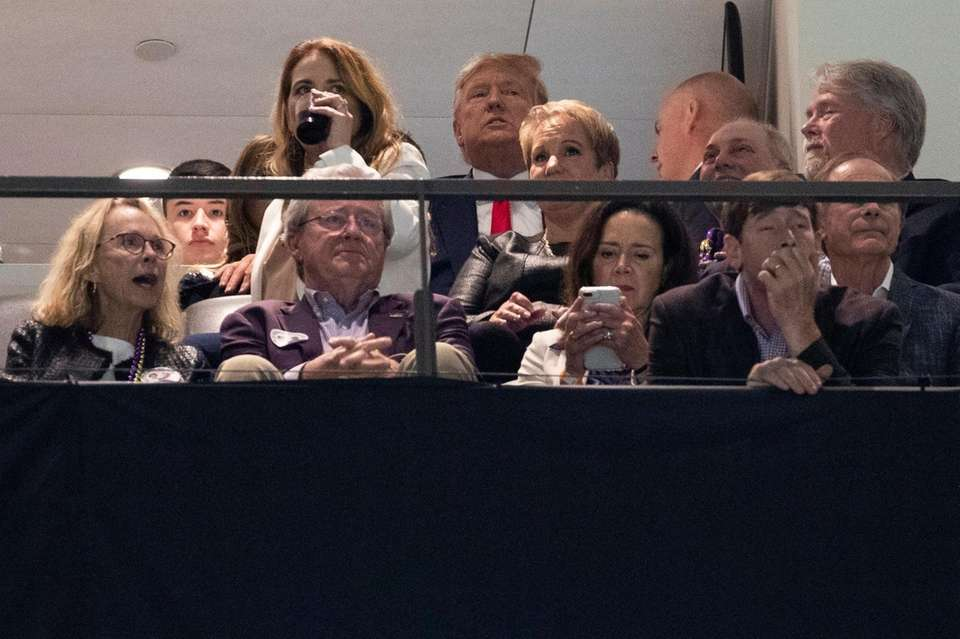 President Donald Trump watches the College Football Playoff