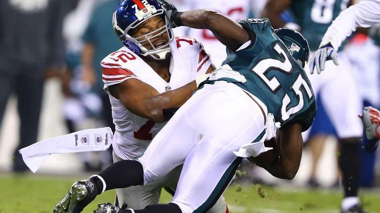 Osi Umenyiora #72 of the Giants tackles LeSean