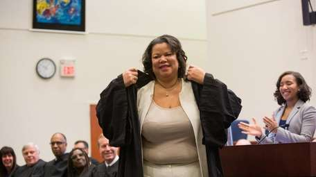 Victoria Gumbs-Moore dons her robe during a judicial