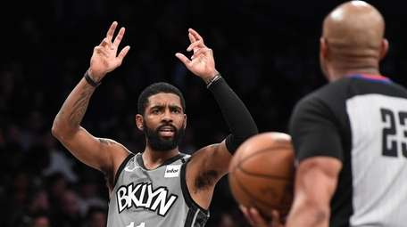 Nets guard Kyrie Irving questions a call during