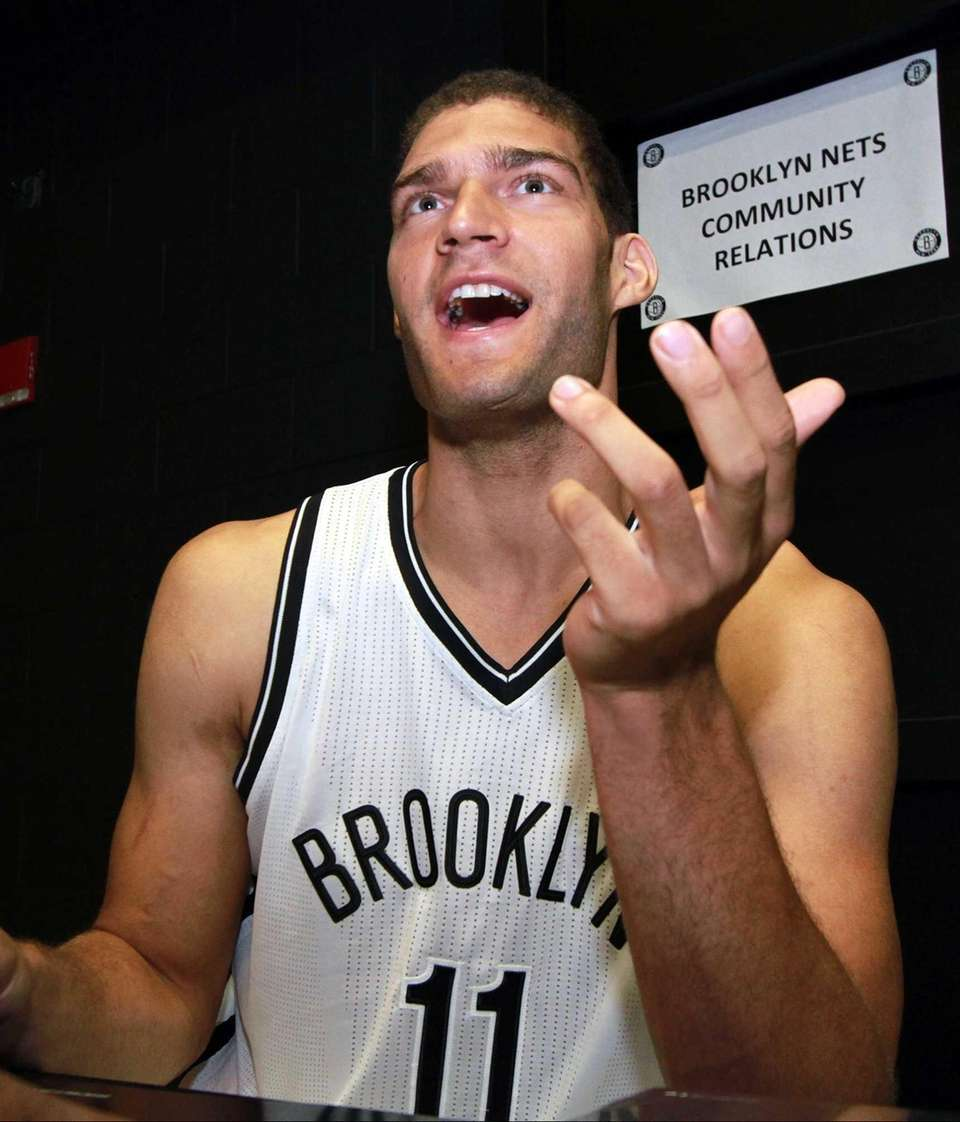 Brook Lopez signs Nets merchandise during the first