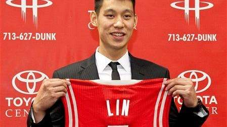 Jeremy Lin poses with a Houston Rockets jersey.