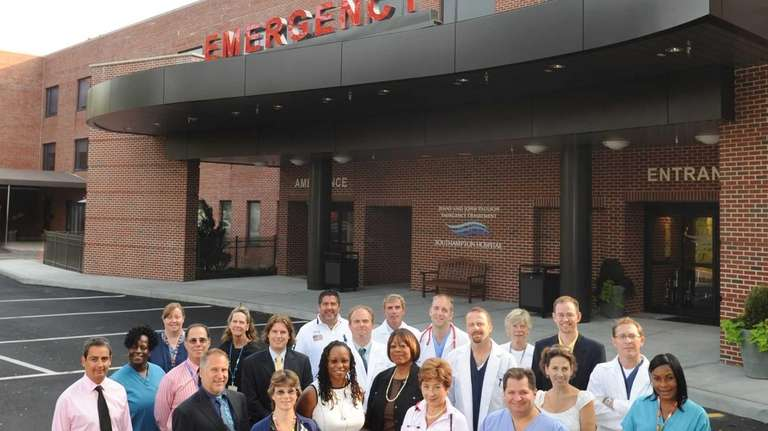 Physicians, nurses and clinical support staff pose outside