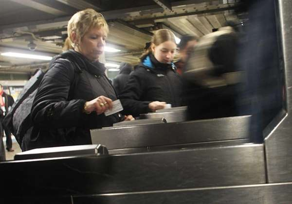 People swipe their metro cards in the New