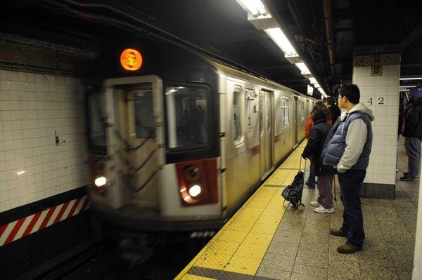 New York City commuters wait on a platform