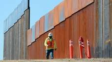 Construction workers build a secondary border wall on