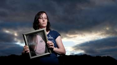 Melissa Cann holds a portrait of her sister,