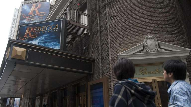 People walk by advertisements for the the cancelled