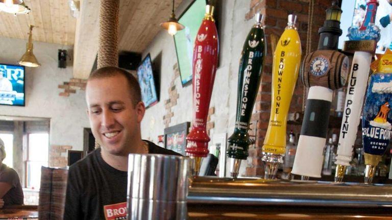 Bartender Steve Carminio behind Brownstone Brewing Company's bar,