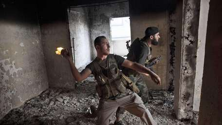 A Free Syrian Army soldier throws a petrol