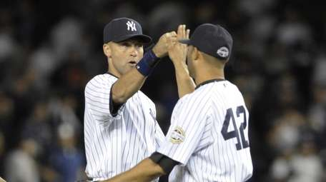 Derek Jeter and Mariano Rivera celebrate after beating