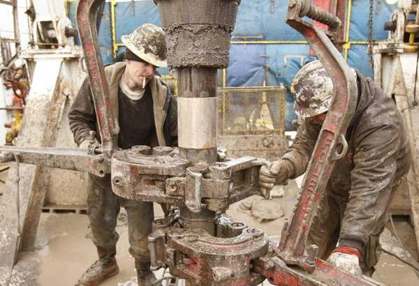 Rig workers drill a saltwater well to get