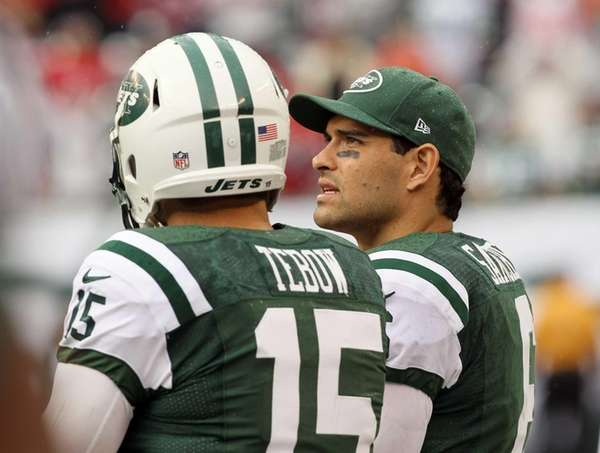 Mark Sanchez and Tim Tebow look on late