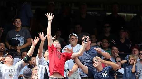 Fans reach for a foul ball during a