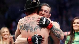 "Conor McGregor, rear, embraces Donald ""Cowboy"" Cerrone after"