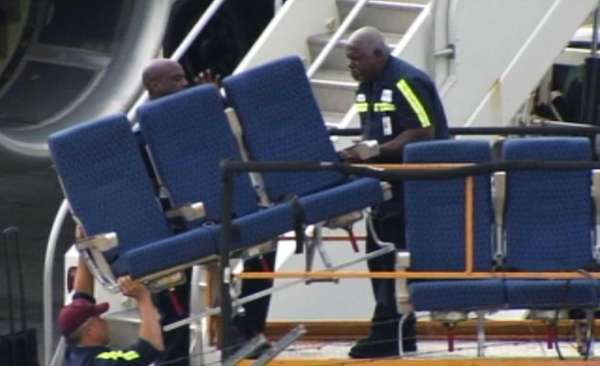 Workers remove seats from an American Airlines 757