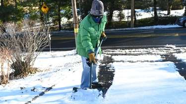 Judith Grinberg shovels snow in front of her